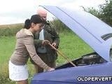 Dziadek pomaga nastolatce przy samochodzie