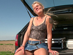 Old chick in the trunk of a car fucks her hot vagina
