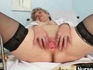 Busty granny in uniform stretching her aged pussy