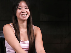 This Asian chick looks extremely excited about her first BDSM session