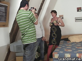 Old mature in red lingerie takes two cocks