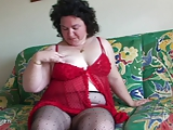 Fat mother playing with a dildo on the couch