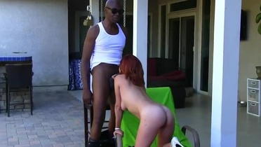 Seducing redhead Ashley Graham performing in an interracial porn video outside