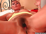 Grandma with hanging big tits is dildoing her hairy cunt