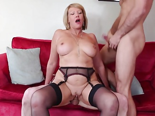 Busty British Milf Takes On A Couple Of Young Cocks